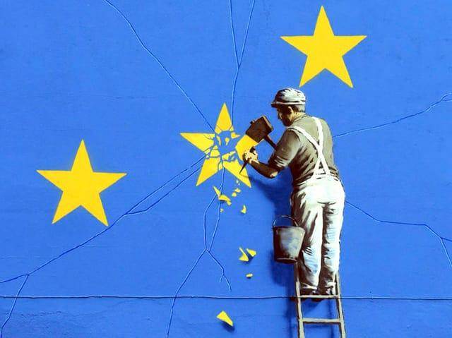 Auf einem Wandgemälde ist ein Mann abgebildet, der einen Stein aus dem Sternenkreis Europas herausmeisselt.