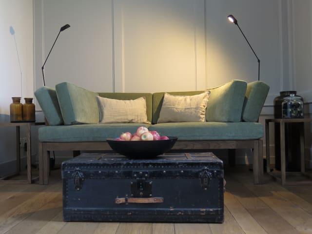 Grünes Sofa mit alter Koffer als Tischchen davor.