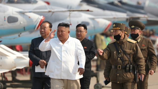 Kim in weissem Hemd, umringt von Militärs, einige tragen schwarzen Mund- und Nasenschutz, dahinter aufgereiht Kampfflugzeuge.
