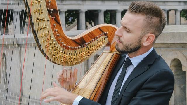 Ein junger Mann spielt Harfe.