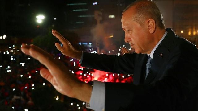 Erdogan mit erhobenen Händen in der Nacht, unten viele Lichter von Anhängern.