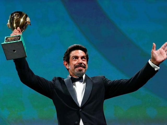 Der Mann hält seine Auszeichnung in die Höhe und winkt mit der anderen Hand der Menge zu.