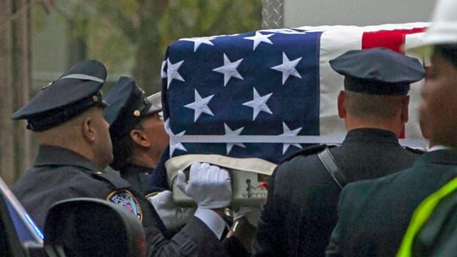 Uniformierte Männer tragen einen Sarg, auf dem die US-Flagge angebracht ist