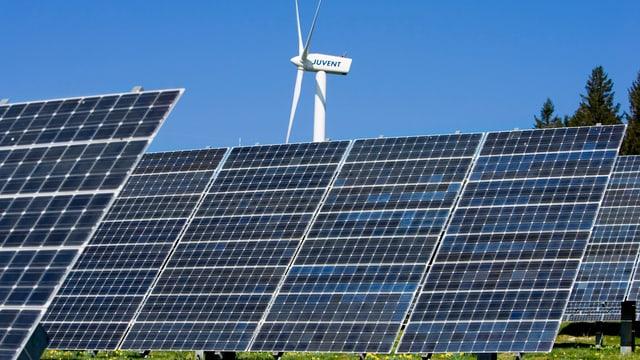 Sollarkollektoren vor einer Windkraftanlage.
