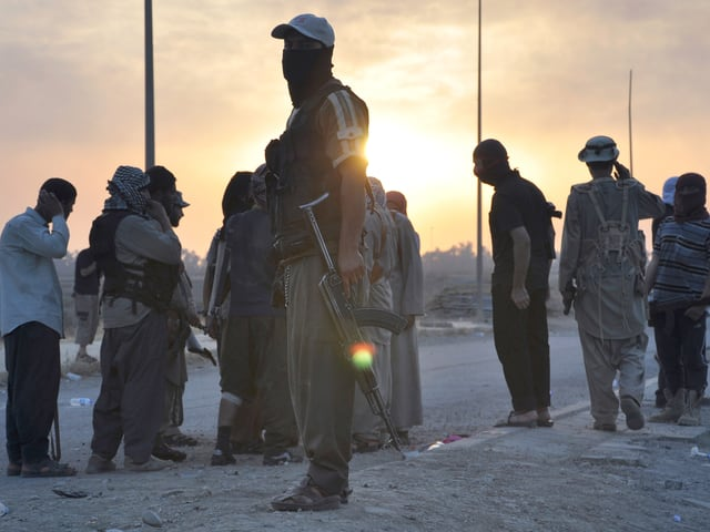 Bewaffnete und vermummte Männer stehen auf der Strasse im Irak.