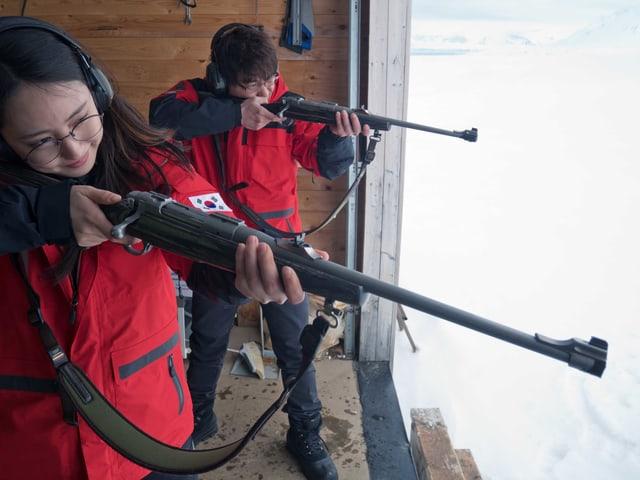 Zwei junge Leute schiessen in der Arktis.