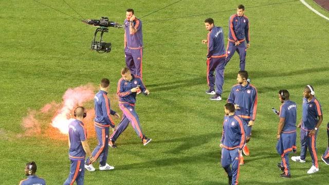 Panathinaikos-Fans feuern Leuchtraketen auf die Piräus-Spieler ab. Diese versuchen sich vor den brennenden Geschossen in Sicherheit zu bringen.