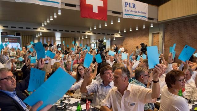 FDP-Delegierte stimmen mit erhobener blauer Stimmkarte ab.