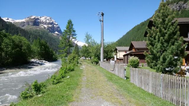Eine Häuserzeile, nur durch einen Gehweg vom Fluss getrennt.
