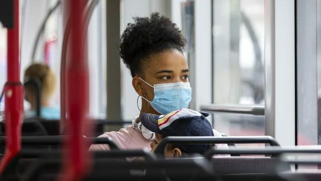 Eine Mutter sitzt im Bus mit ihrem Sohn und zeigt aus dem Fenster, beide tragen Masken.