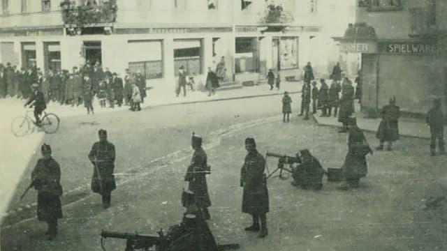 Männer mit Maschinengewehren in Grenchen auf einem öffentlichen Platz.