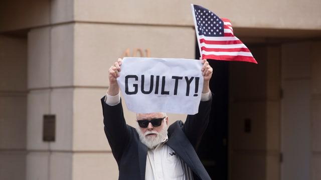 Mann mit «Guilty»-Plakat.