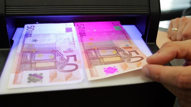Ein falscher und ein echter 50-Euro-Schein unter einer Fluoreszenz-Leuchte.