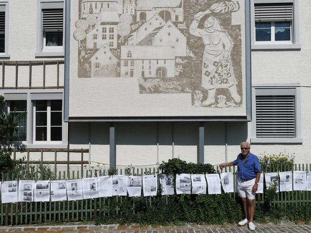 Ein Mann steht vor einem Gartenzaun und dem Wandbild