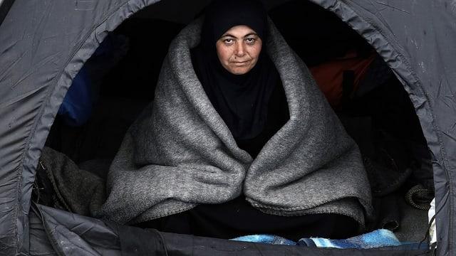 Frau sitzt mit Decke in einem Zelt.
