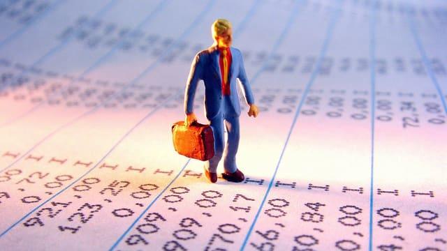 Ein Spielzeugmännchen steht auf einem Blatt mit Buchhaltungszahlen.