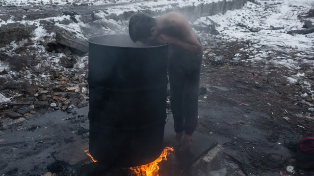 Ein Junge beugt sich in eine Abfalltonne, unter der ein Feuer brennt. Er trägt nur eine Hose und es liegt Schnee.