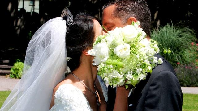 Brautleute, die sich küssen.