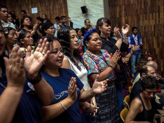 Nobelpreisträgerin Rigoberta Menchú und weitere Zuschauer im Gerichtssaal applaudieren.