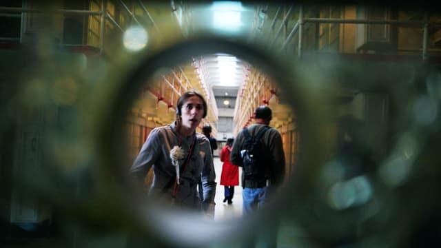 Blick durch eine runde Öffnung: Eine Frau starrt in die Kamera.