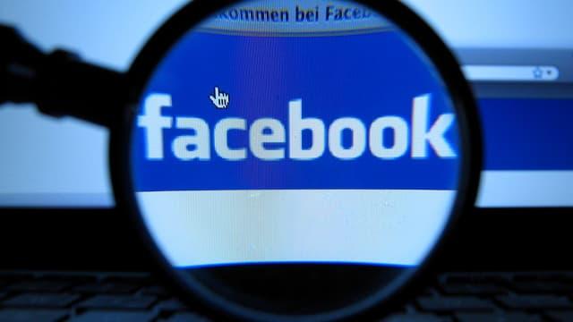 Eine Lupe vor einem Bildschirm, auf dem Facebook steht.