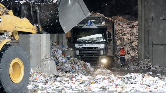 Ein Lastwagen voller Altpapier wird in einer Fabrik entladen.