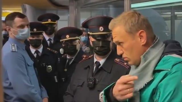 Nawalny und uniformierte Sicherheitskräfte.