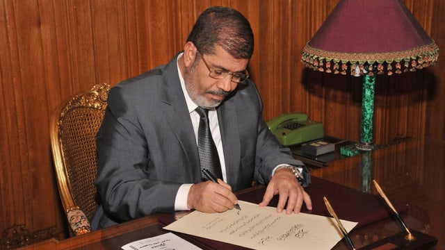Mursi an einem Tisch sitzend.