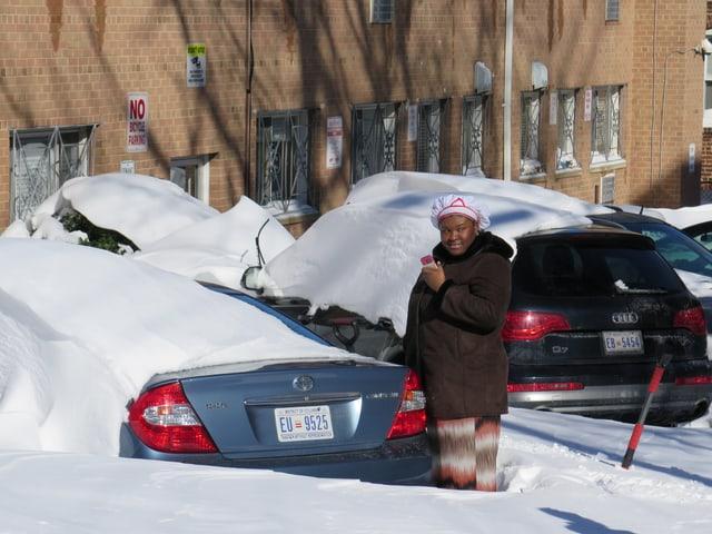 Eine Frau steht vor einem eingeschneiten Auto