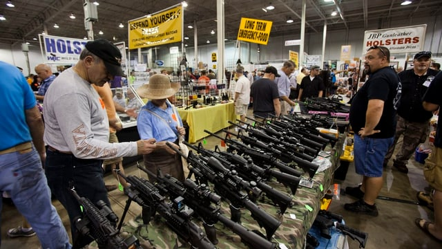 Menschen die Gewehre in einer riesigen Halle betrachten.