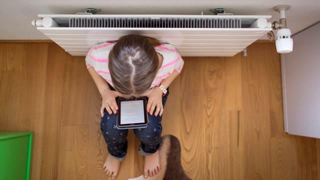 Ein Kind sitzt mit seinem Tablet an einem Radiator und liest. (keystone)