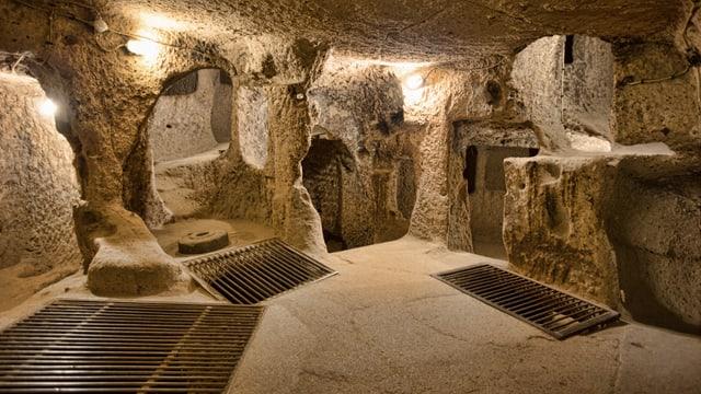 Höhle mit Durchgängen und Treppen und Gitter über Öffnungen auf dem Boden
