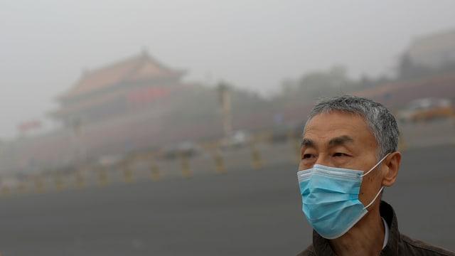 Mann mit Maske, es ist rauchig. Hinten sieht man ein chinesisches Gebäude.