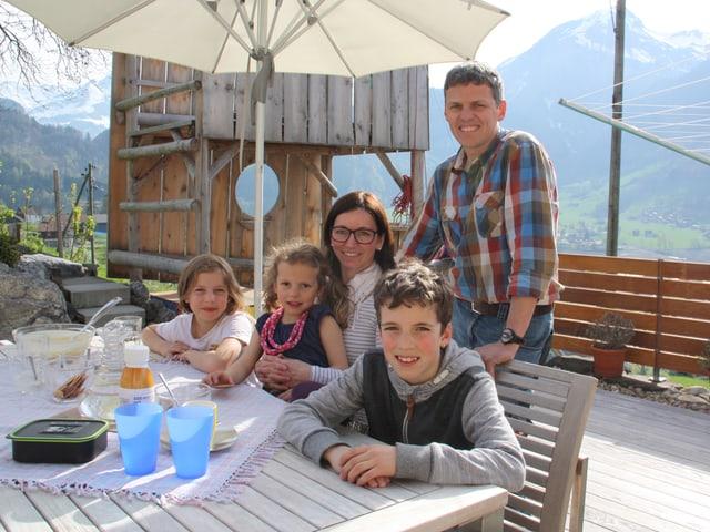 Eine fünfköpfige Familie sitzt auf einer Terrasse an einem Holztisch.