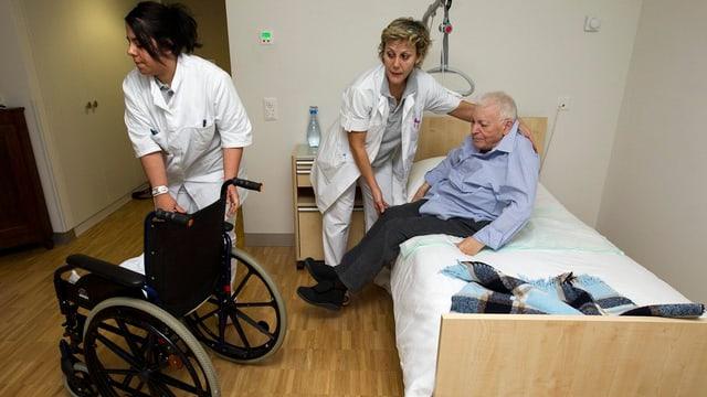 Pflegerinnen in einem Pflegeheim helfen einem pflegebedürftigen Senior aus dem Bett.