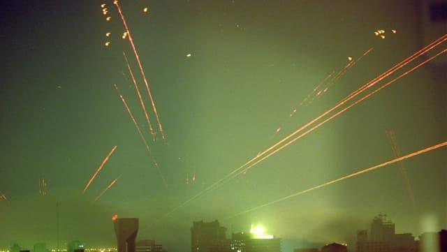 Es fallen Bomben auf Bagdad. Man sieht helle Lichtstreifen in der dunklen Nacht.