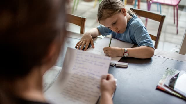 Mädchen schreibt am Küchentisch, Mutter hält Papier in der Hand