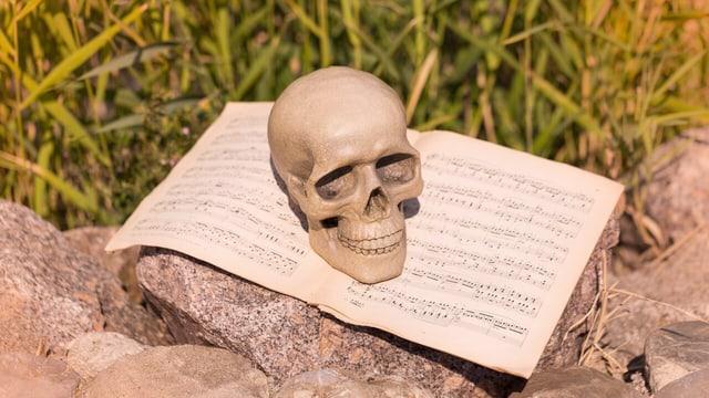 Ein Totenkopf liegt auf einem Notenheft.