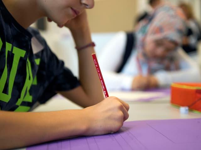 Ein Junge schreibt auf ein Papier