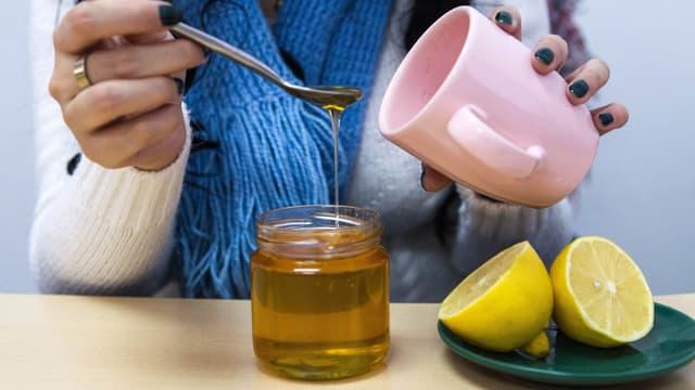 Frau löffelt Honig in eine Teetasse