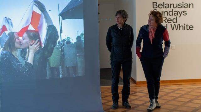 Blick in den Ausstellungsraum: Zwei Frauen schauen auf eine Leinwand, auf die eine Fotografie projiziert wird.
