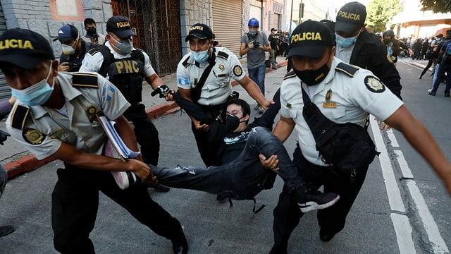 Polizisten tragen einen Demonstranten.