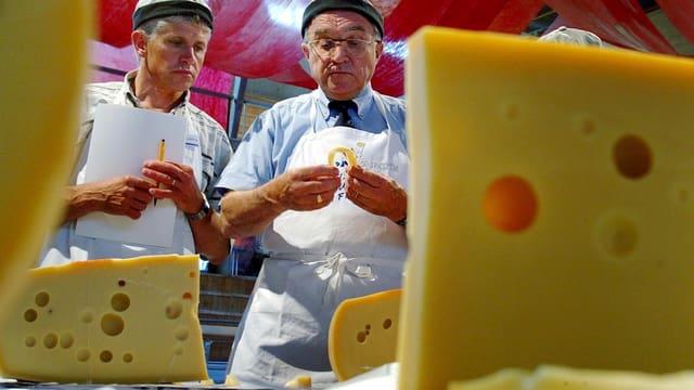 Zwei Käsepezialisten bei der Degustation eines Emmentalers.