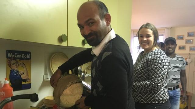 Ein Mann mit einer Pfanne voll Reis steht in einer Küche, daneben eine Frau.