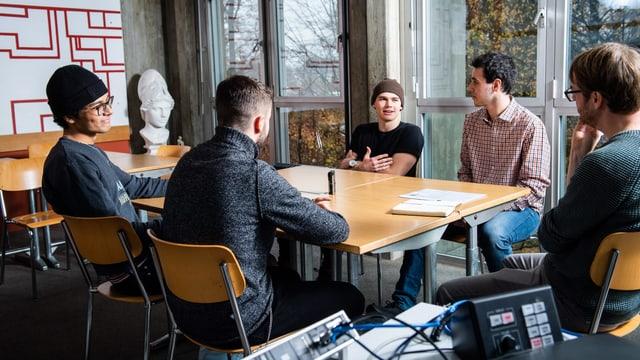 Fünf Männer sitzen in einem Schulzimmer um einen Tisch.