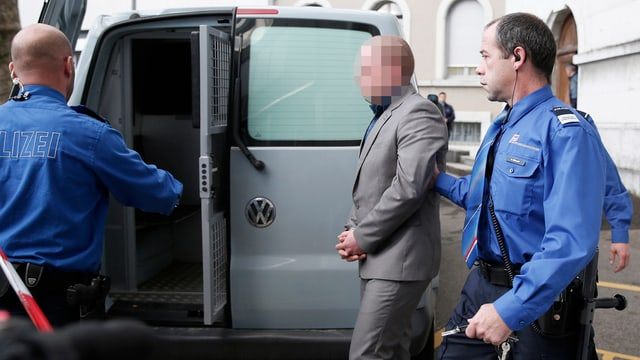 Polizisten führen verurteilten Mörder zu einem Kastenwagen.