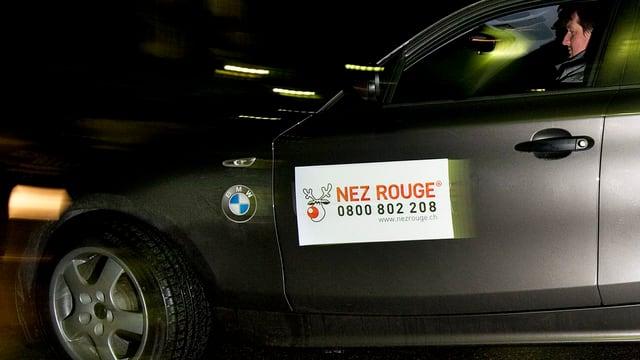 Ein schwarzes Auto des Fahrdienstes «Nez Rouge» fährt durch die Nacht.