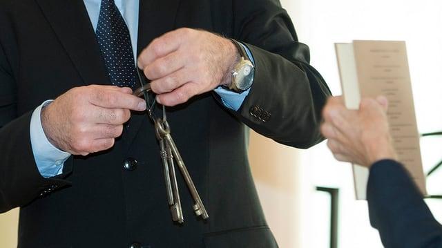 Ueli Maurer hält die Schlüssel in der Hand und Widmer-Schlumpf übergibt ihm das Gotthelf-Buch.