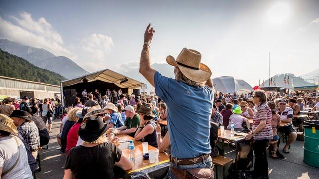 Ein Mann mit Cowboyhut klatscht in die Hände.