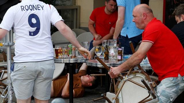 Ein englischer Fan hält einen Stuhl in der Hand.